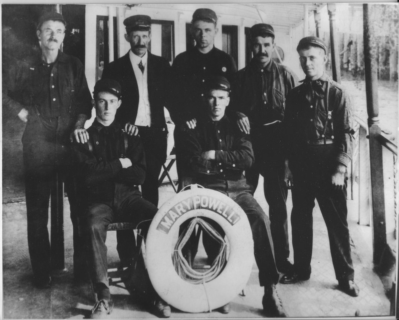 7 members of Mary Powell crew on deck, 1908. In back row, second from left is first pilot William B. Mains and second from right is Philip Mains, mate.  Front row left is Arthur A. Warrington. Hudson River Maritime Museum collection.