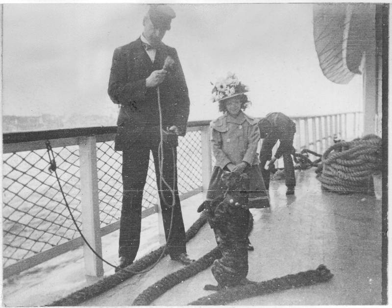 Captain A. Eltinge Anderson shakes the end of a line at Buster, balanced on his hind legs, aboard the Mary Powell. Young Elizabeth Hasbrouck looks on. Capt. Anderson may be holding a small camera in his left hand. Donald C. Ringwald Collection, Hudson River Maritime Museum.