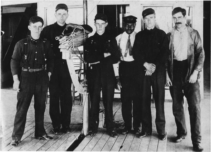 Deck hands and either engineer or water tender (Black man in white shirt with tie) of the Mary Powell, standing next to a fire hose. Third from left – Arthur Warrington. Donald C. Ringwald Collection, Hudson River Maritime Museum.