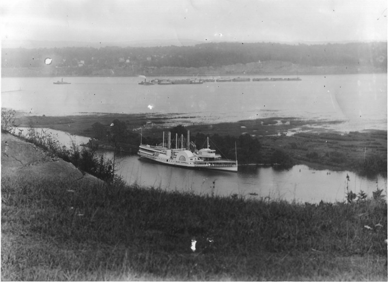 Mary Powell at Sunflower Dock along south shore of Rondout Creek, as seen from above. In the background, a tugboat tows a long string of barges on the Hudson River. Donald C. Ringwald Collection, Hudson River Maritime Museum.